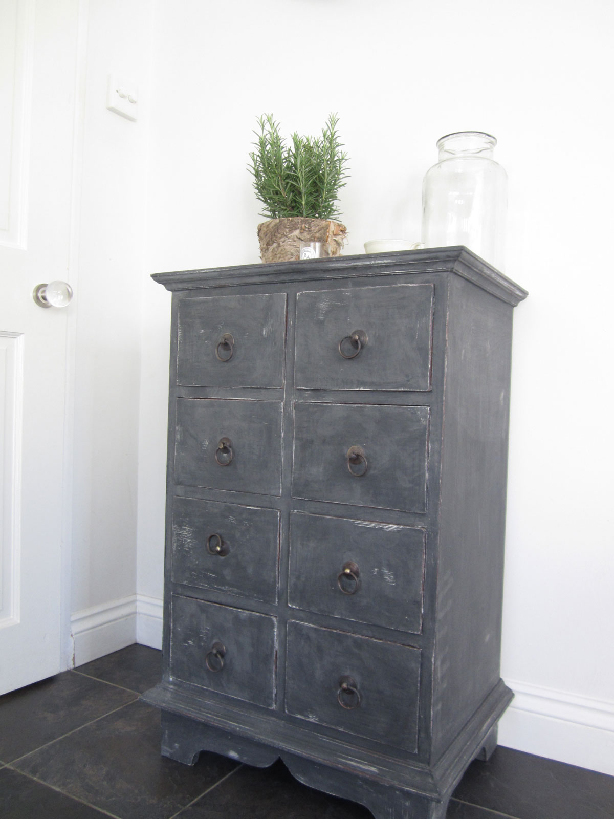 This old dark wood set of drawers got a gun metal look with a layer of chalk paint in differing tones