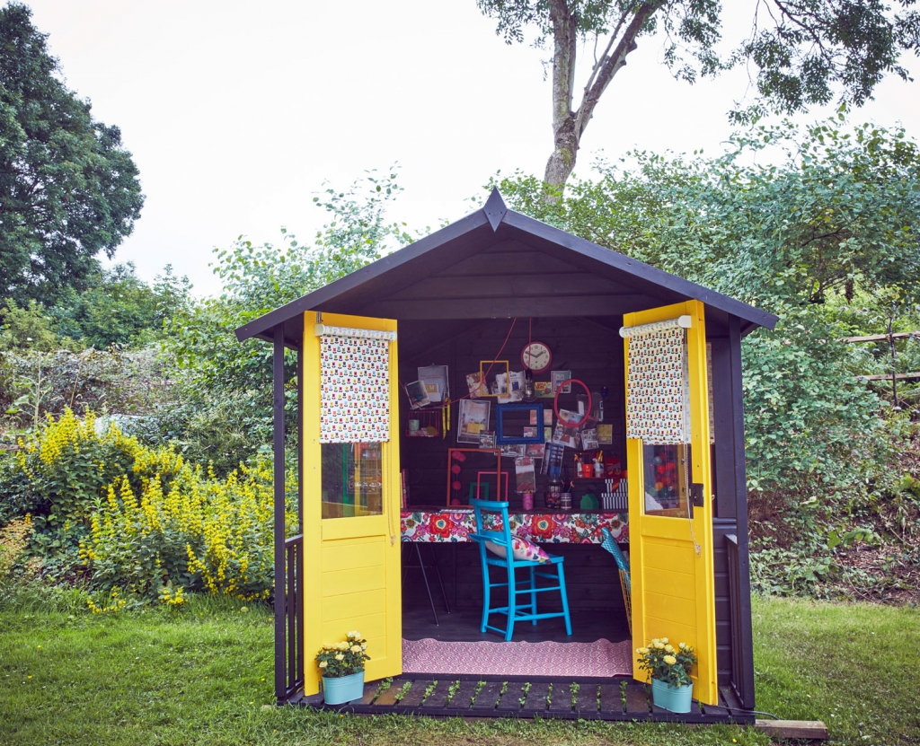 A She shed designed as a crafting DIY and upcycling creaive workspace at the end of the garden. The balck weatherboard exterior is set off by bright yellow doors and patterned fabric blinds