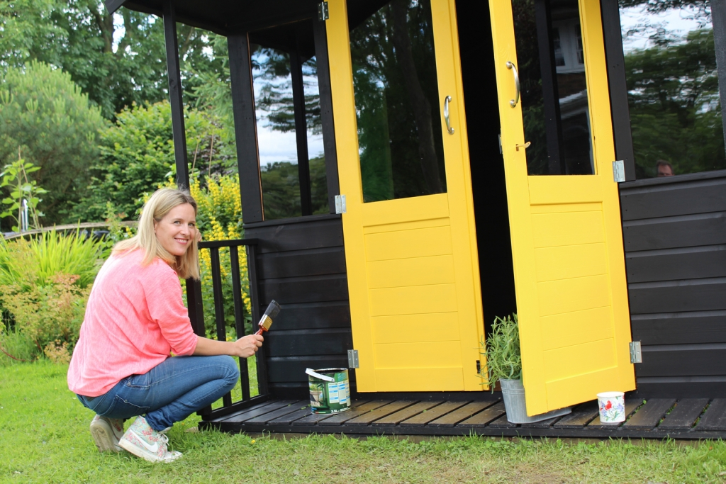 Painting a shed in a black ash deckstain with bright yellow exterior doors make a strong colour statement