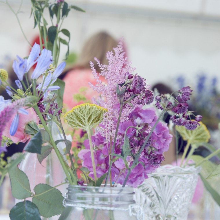 arrange summer garden flowers in a collection of containers