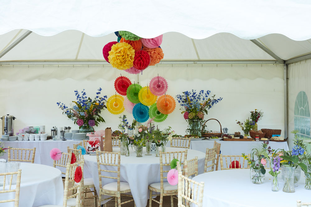 Create a big imapct insde the plain marquee by grouping affordable paper decorations. rather than scattering athem around the marquee group them all togther to make a stronger impact.