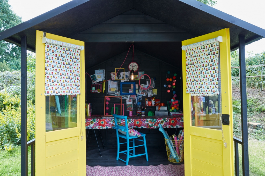 Sophie Robinson interior designed this she shed to be a creative work space where she could do ctaft projects, diy and upcycling. The dark walls work brilliantly with the opos of colour