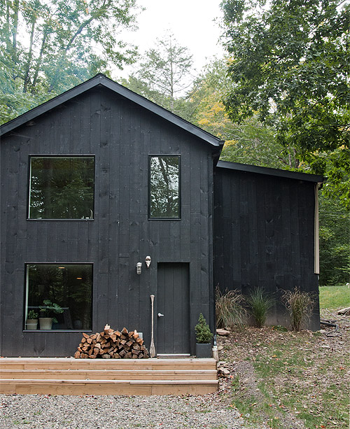 black weatherboard house with wood cladding in the woods