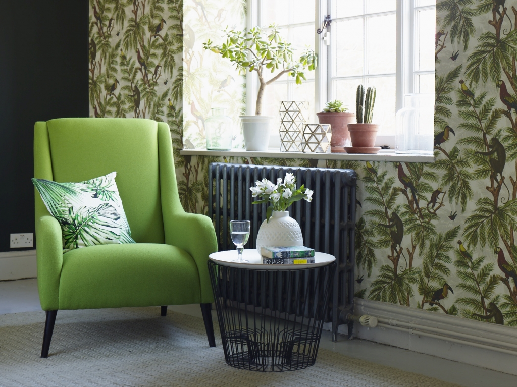 Green armchair in tropical trend living room with botanical print cushion styled by Sophie Robinson
