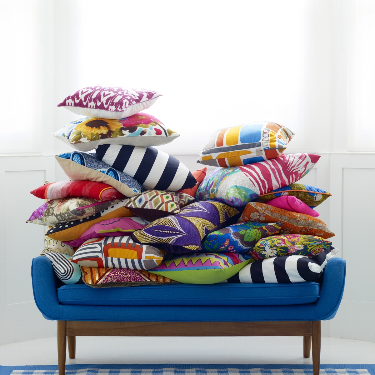 Blue sofa with a pile of pattern clash fabric cushions. Image styled by Mary Norden
