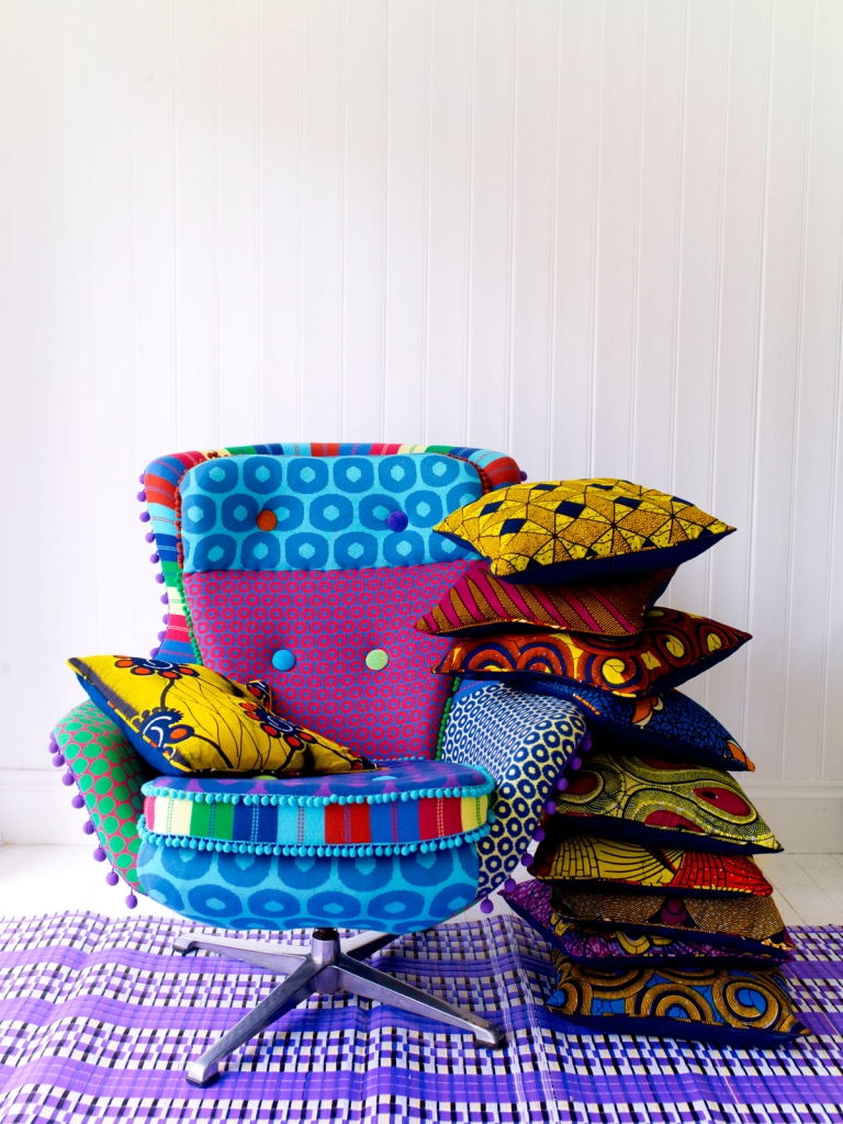 eames egg chair upholsterd in African wax prints and pom poms. Image styled by interior stylist mary norden