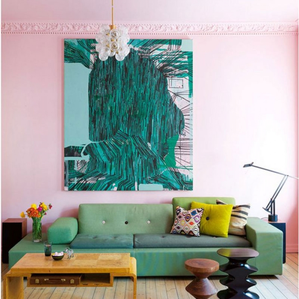 Pale pink walls and shots of emerald green artwrk and green sofa make this living room look stunning.