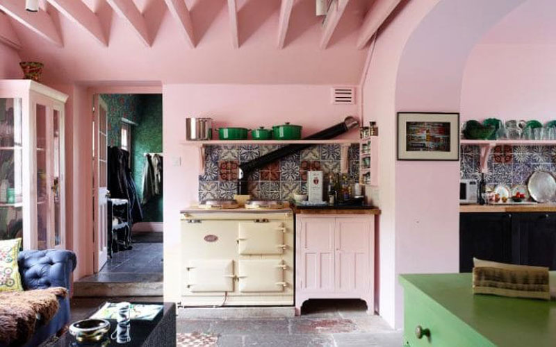 Pale pink kitchen with green le cruset pots and a cream aga. From the home of Solage Azagury Partridge