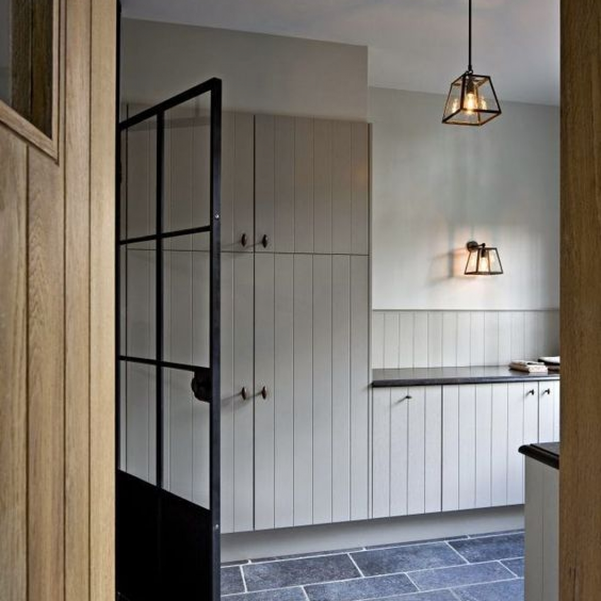 V groove T&G kitchen units with slate floor and Crital door