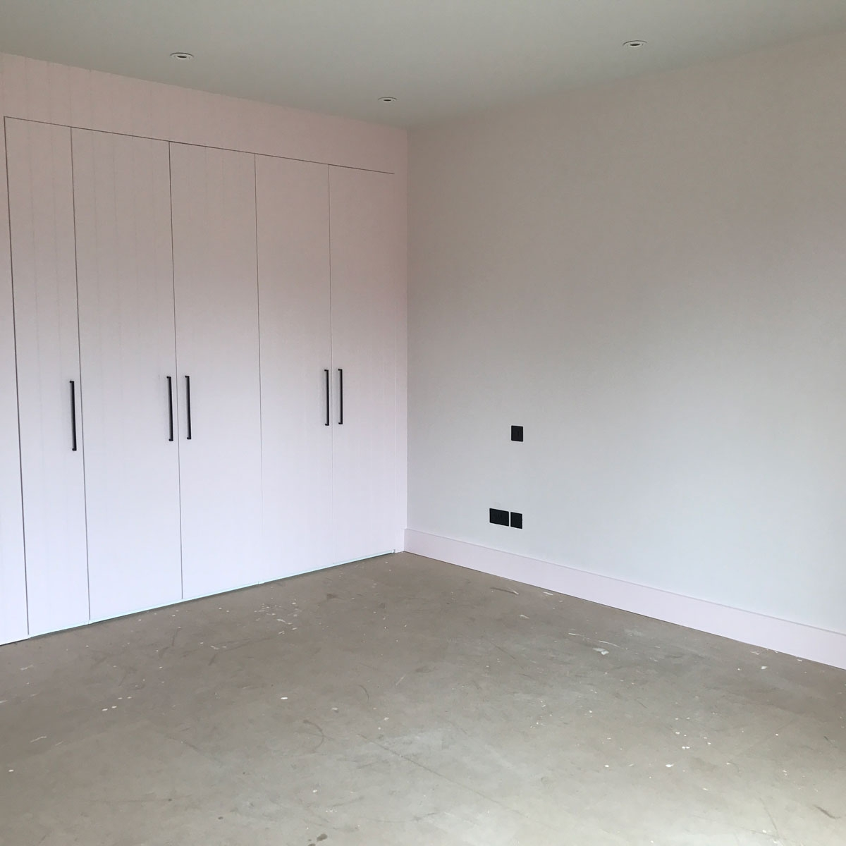 pink bedroom painted in Nevada 6 by Dulux with fitted tongue and groove wardrobes and black sockets and light switches