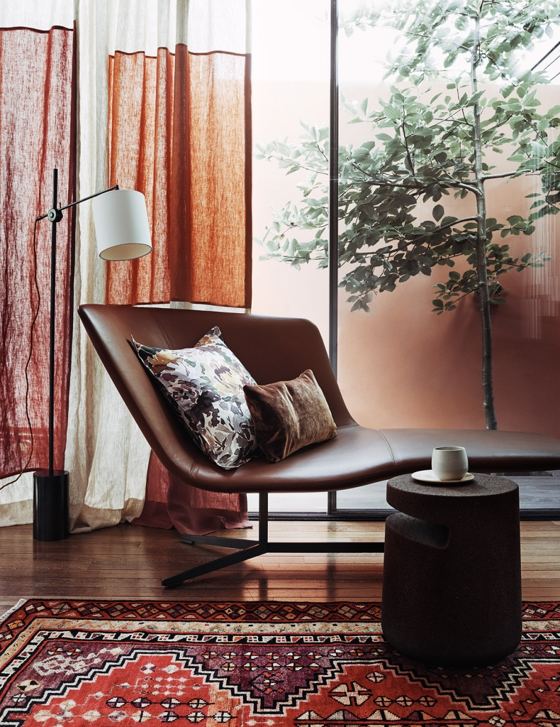 Statement armchair in smooth brown leather sits elegantly next to raw linen drapes and a oriental rug. Styled by Claudia Bryant for Homes and Gardens