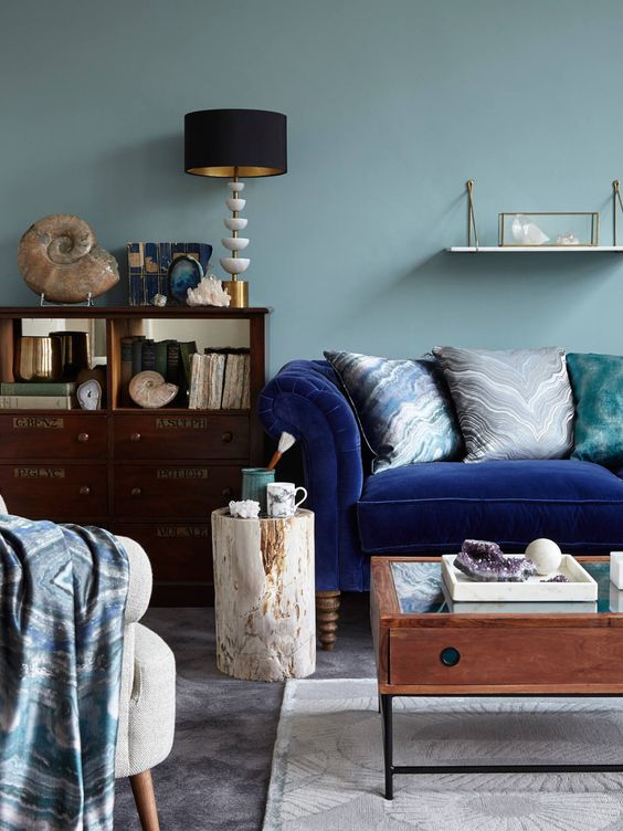 A blue chesterfeild velvet sofa looks sumptuous next to an old plan chest and a collection of vintage books and artefacts. This is the perfect cosy living room for the Autumn personality