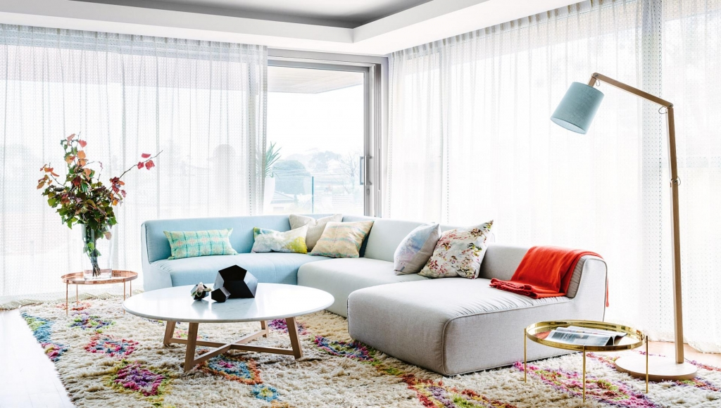 Light and airy living room with wrap around large windows with voiles. Pastel modular sofa with morrocan berba rug and brass side table