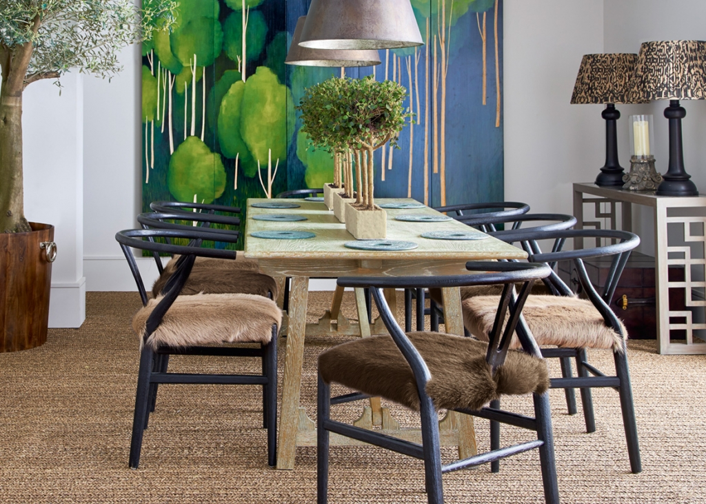 A striking rustic dining room with raw hide upholstered chairs and a raw wood dining table. Striking artwork in intense colours is great for the Autumn personality, according to colour psychology