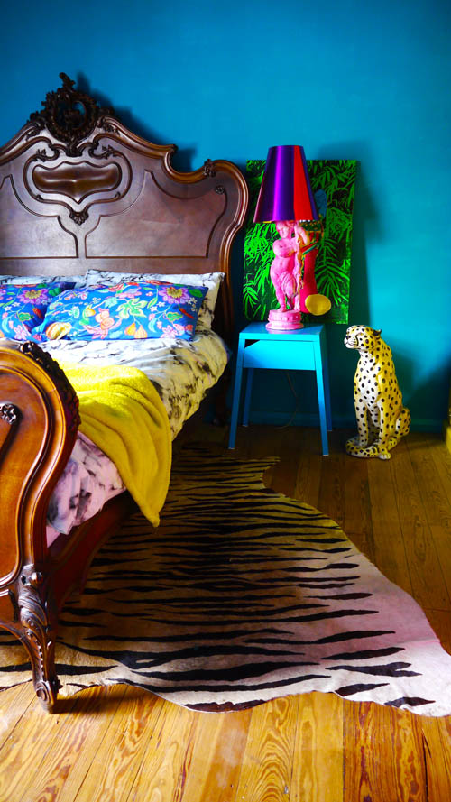 Interior design should have an element of fun. Like this deep blue bedroom with lepaord print ornament and neon pink bird table lamp for example. Just one of the ways to make a happy home