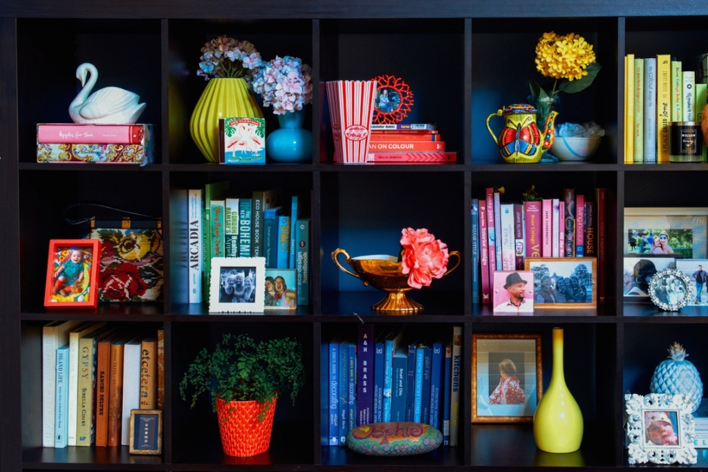 Interior deisgner sophie robinson styles her shelves with books and family photos. She even goes so far as colour coding the books on the book shelf for a fully styled look