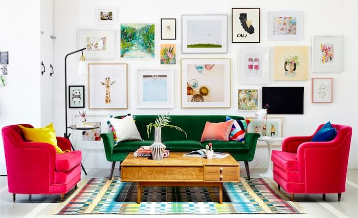 Velvet green sofa sits below gallery wall, as styled by interior deisgner Emily Henderson. Twin pink tub armachirs and a multi coloured rug are perched under the mid century modern coffee table