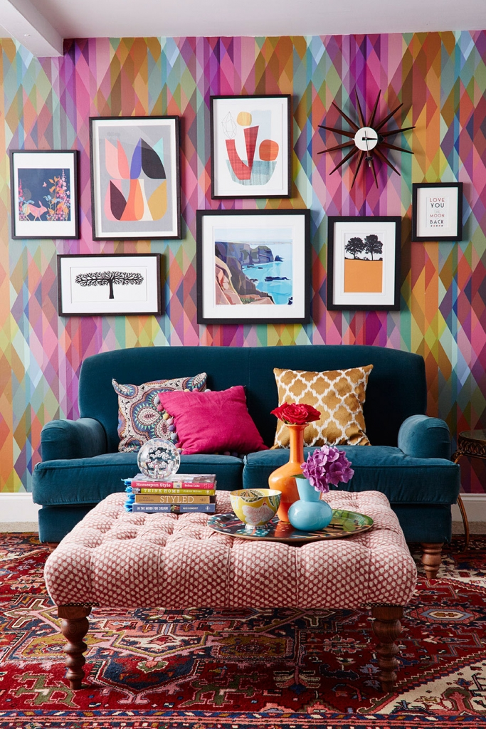 How to hang artwork in a gallery wall style. Inside the colourful home of interior designer and stylist Sophie Robinson. The striking prism wallpaper by Cole and Son makes a great back drop to the teal sofa