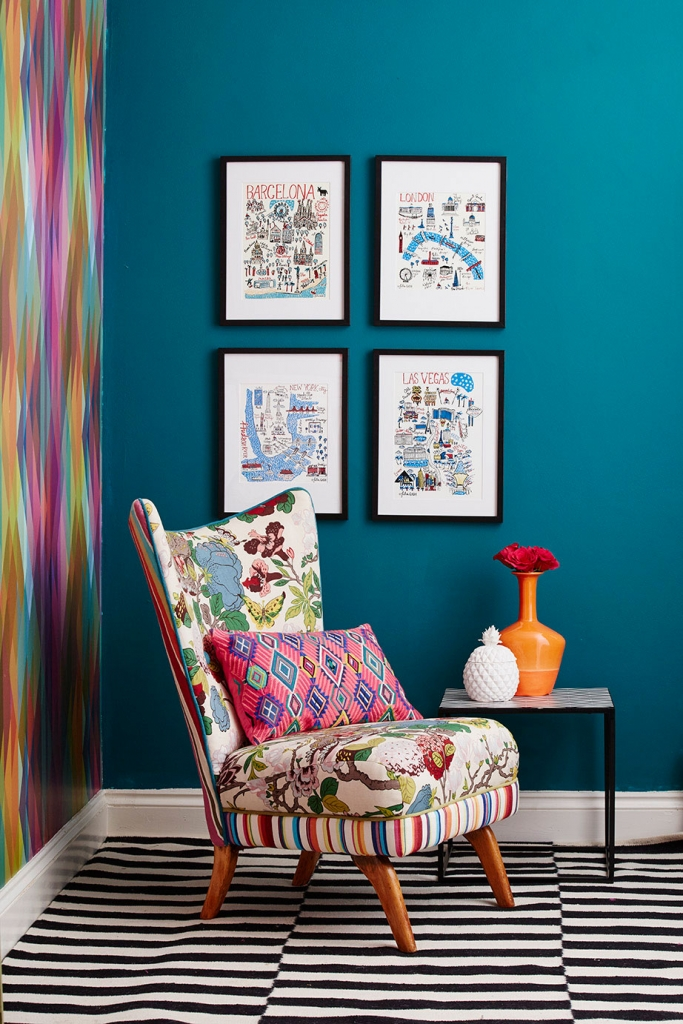 Arranging artwork by hanging pictures in classic symmetry creates a great focal point in an interior design room scheme. dark teal walls shows off the prints really well, as seen in the home of interior designer Sophie Robinson