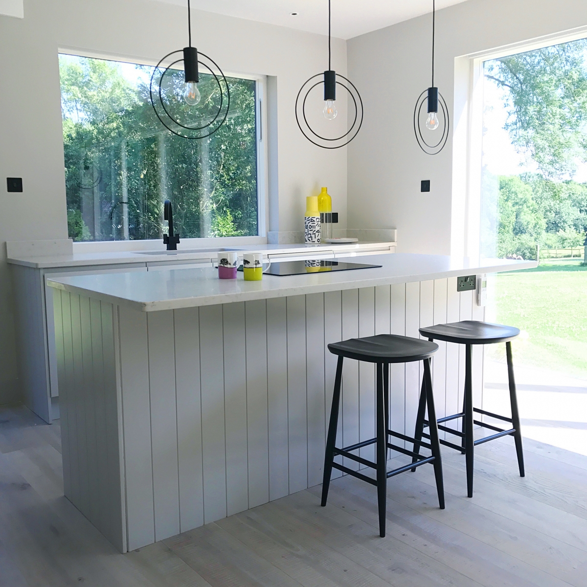 pale grey kitchen with tongue and groove island and black ercol barstools