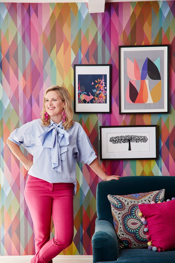 interior designer sophie robinson love shanging artwork in her home decor to make a space feel quirky and colourful. Wearing pink trusers and pale blue blouse with oversized pussy bow