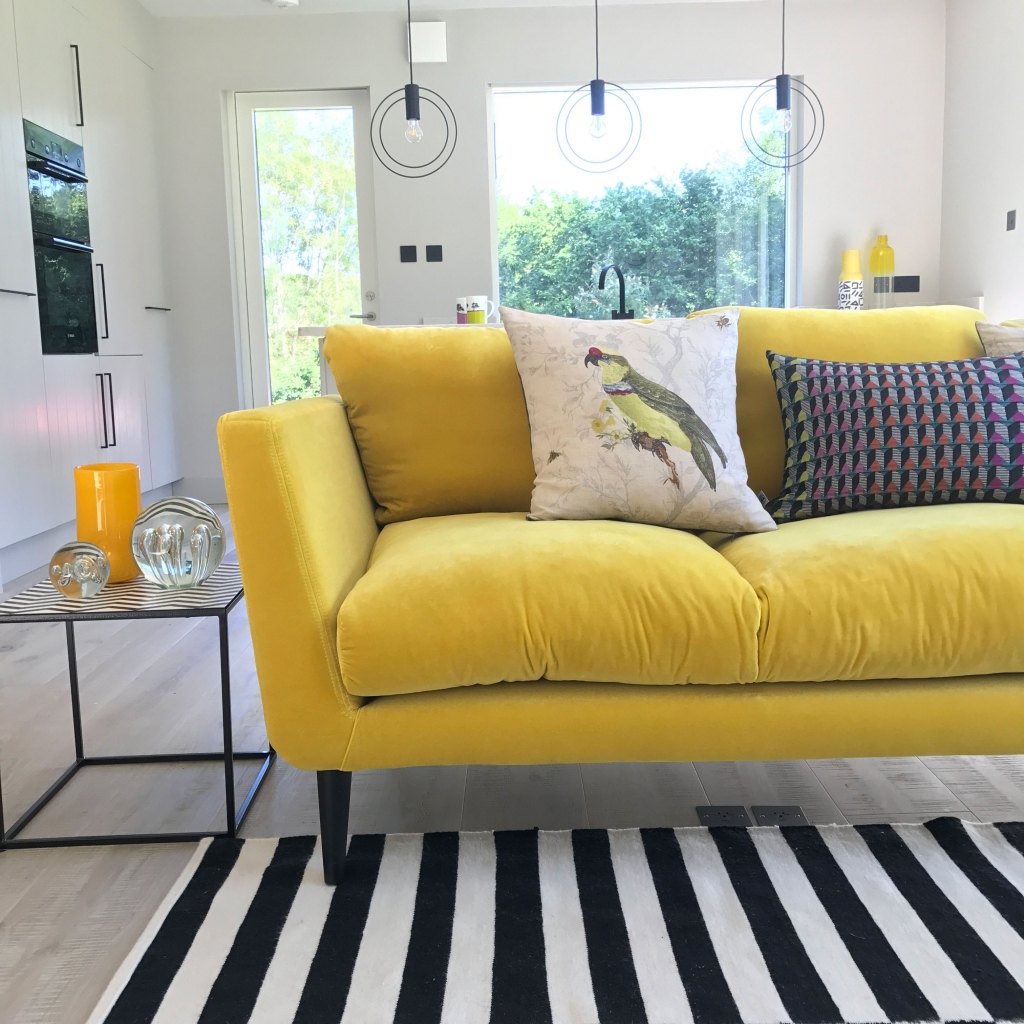 Velvet yellow sofa in the annex of interior designer Sophie Robinson. Black and white monochrome rug goes so wonderfully with the yellow sofa
