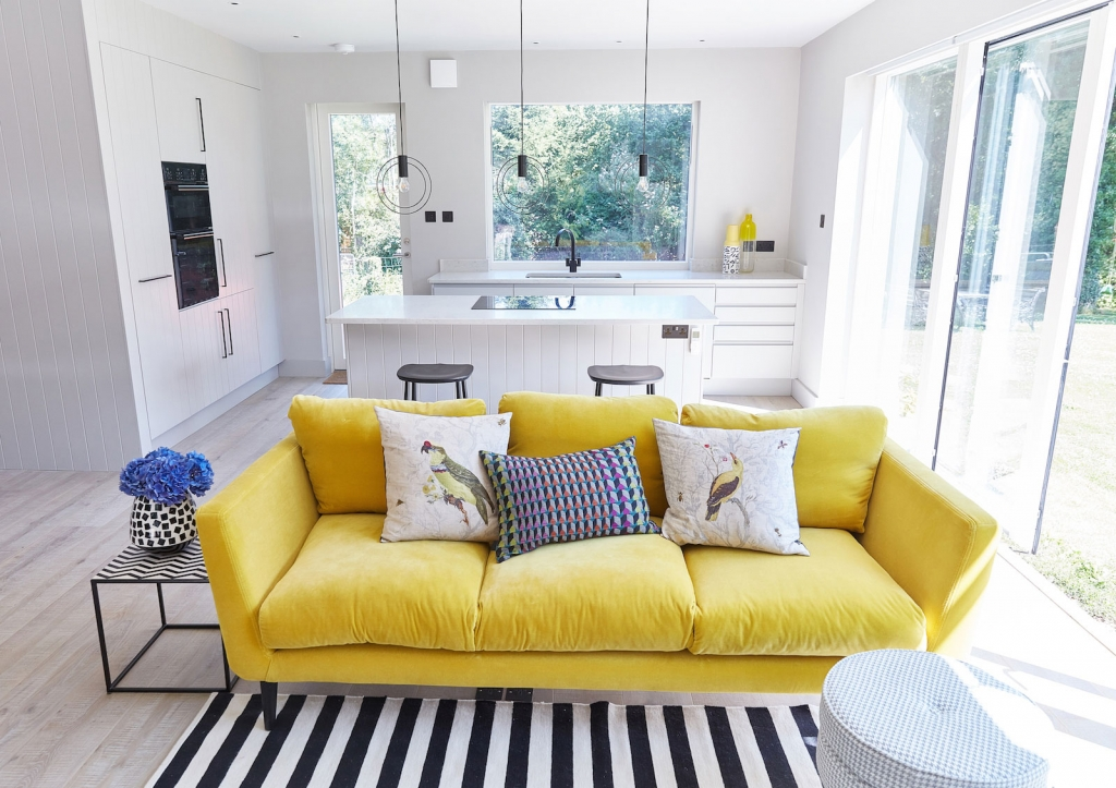 a canary yellow velevet sofa adds a pop of colour to an all great interior. The open plan living room kitchen is at the home of interior designer Sophie Robinson