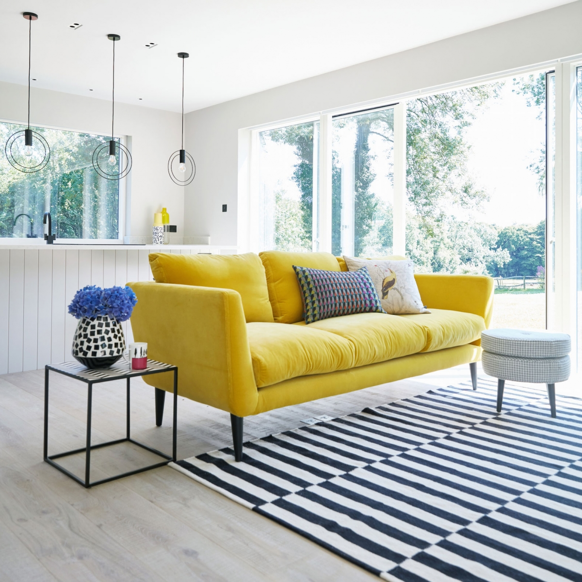 Canaray yellow velvet sofa adds a pop of colour to an all grey living room in the new annex build at the home of interior deisgner Sophie Robinson
