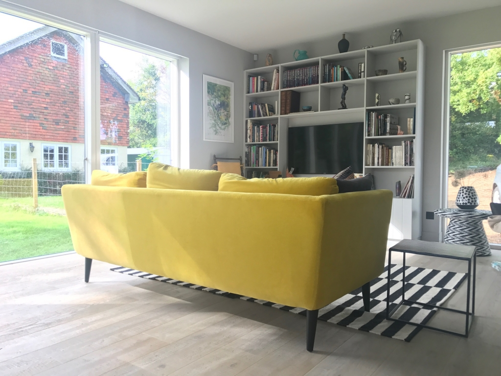 The Holly sofa from sofa.com in canary yellow velvet sits perfectly in a n all grey interior open plan space.