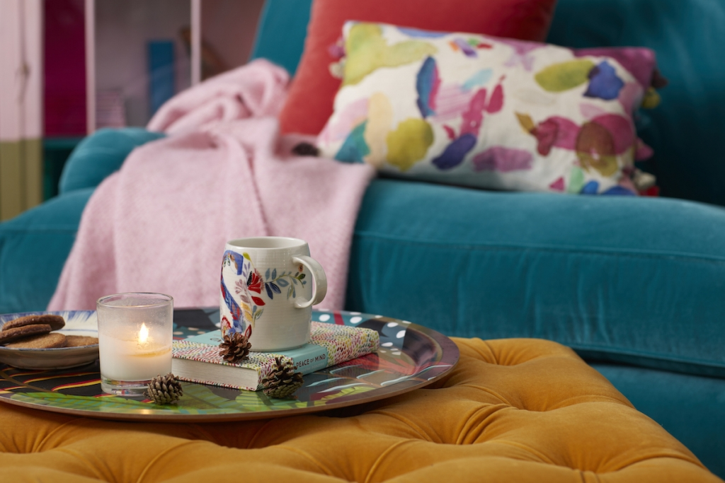 Cosy autumn interior design with button back footstool and scented candles. Designed by Sophie Robinson