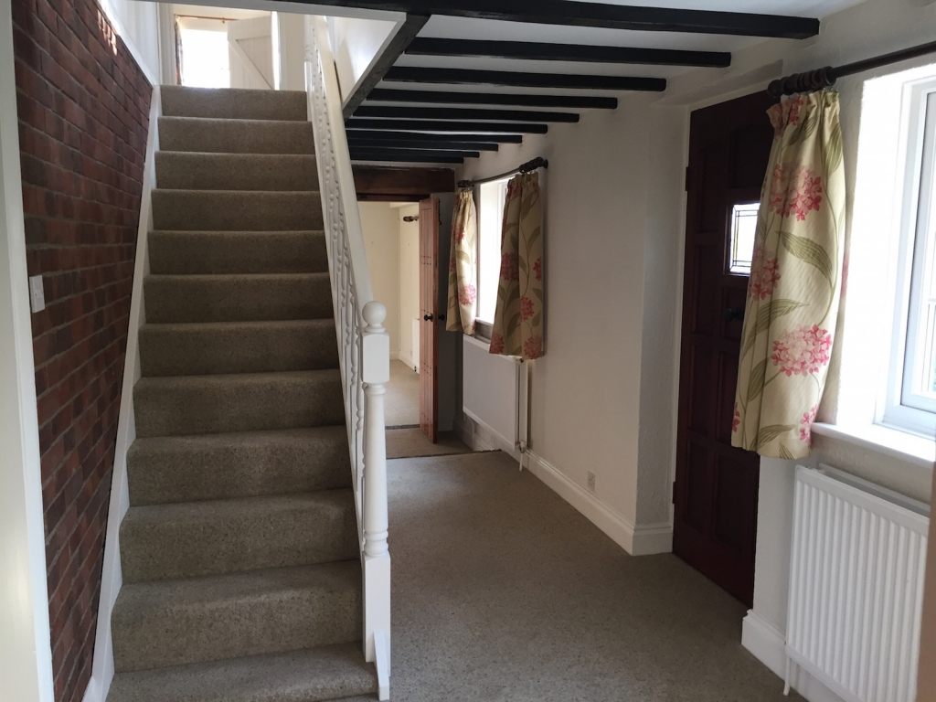 Dated looking hallway with beige carpet and short curtains