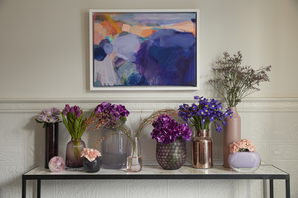 pantone colour of the year 2018 is ultra violet. a simple way to add purple to your interior design colour scheme is with purple flowers. a side board ciollection of vases with iris's, hydrangeas, and tulips is perfect. painting by sophie abbott