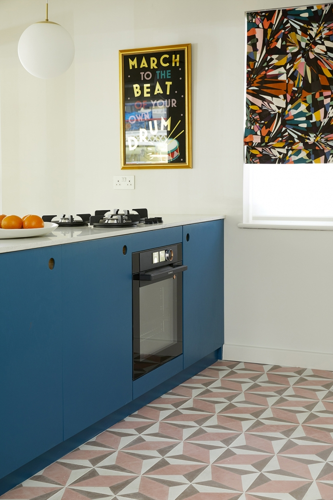 Interior deisgner Sophie robinson designed this marine blue kitchen with pink outra cement tiles from Bert and may.