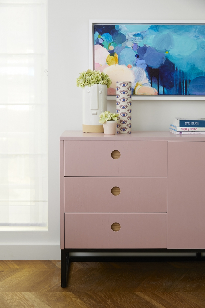A pale pink sideboard from Naked Kitchens matches nicely with the abract artwork by Sophie Abbitt. Interior design by Sophie Robinson