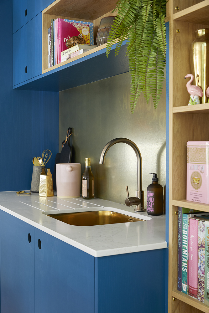 Blue kitchen from Naked kitchens combined with aged brass splash back and gold tap. Interior design by Sophie Robinson