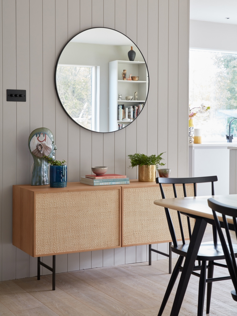 modern country home of interior desiger Sophie Robinson. nautral oak mid century modern sideboard with patsy rund mirror and ercol dining furniture