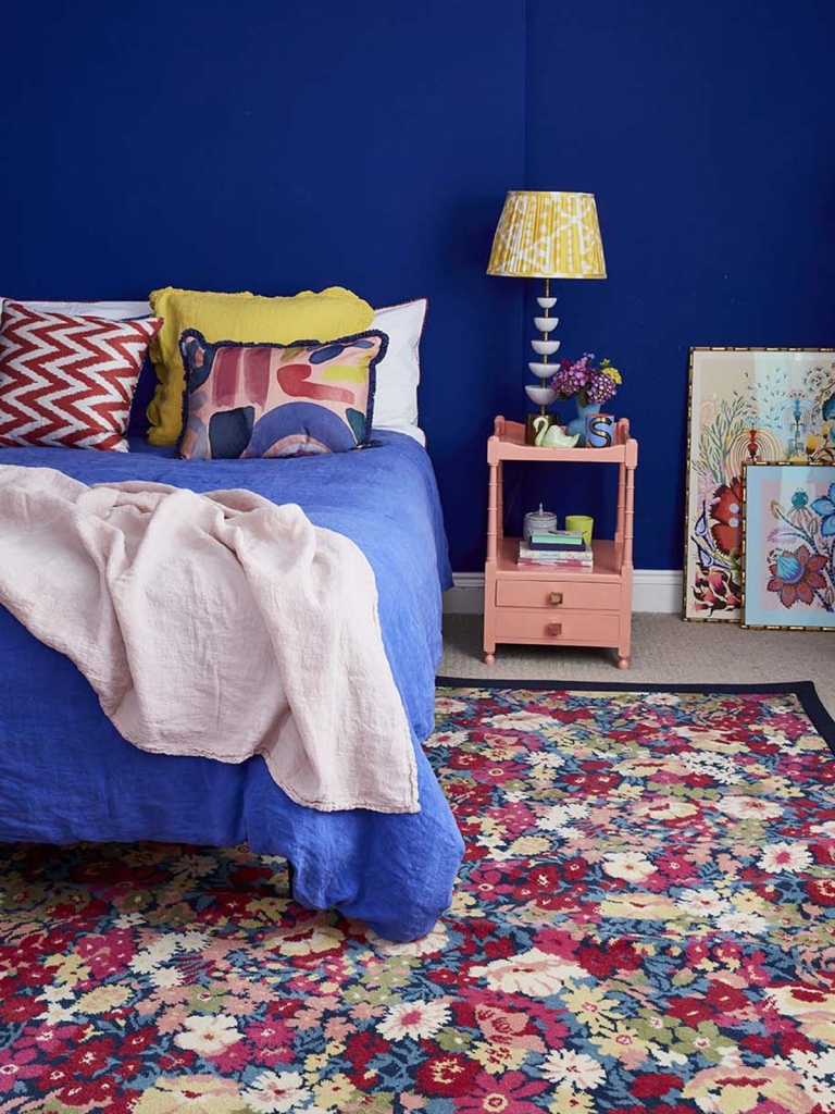 Alternative Flooring rug in the bedroom of interior designer sophie robinson. Liberty flowers of thorpe summer garden rug by Alternative flooring in a deep blue berdoom painted smalt by little greene.