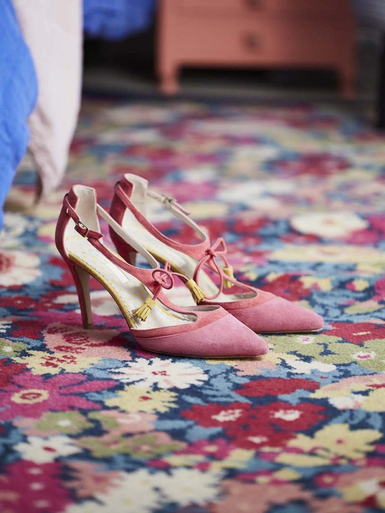 Alternative Flooring rug in Summmer flowers at Thorpe garden by iberty frabrics with detail of pink shoes with tassles in the home of interior designer sophie robinson