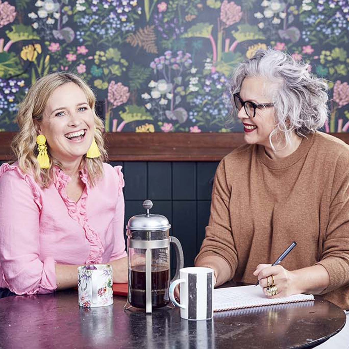 Interior designer Sophie Robinson and journalist Kate Watson-Smyth The Great Indoors podcast, bright floral and rhubarb plants on dark green background wallpaper kitchen