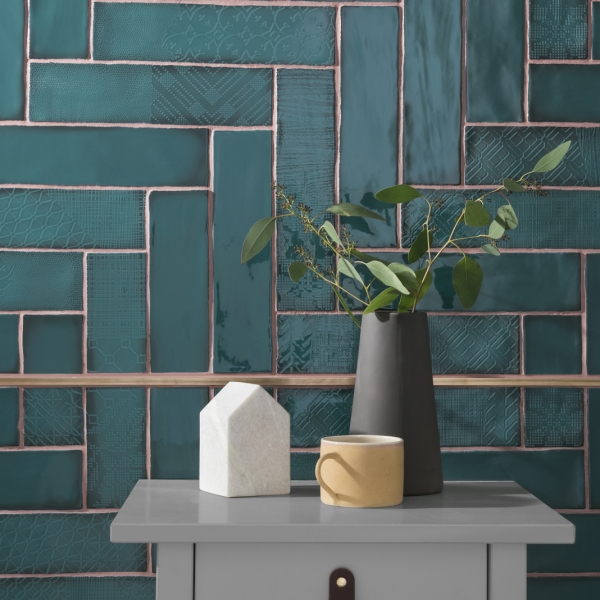 teal brick bond tile arranged in a herringbone formation in a teal bathroom