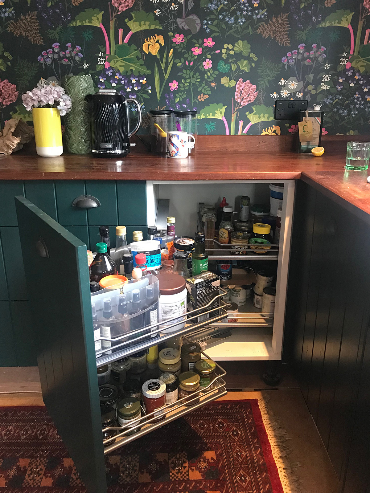 Interior Designer Sophie Robinson's kitchen Boras Tapeter Rabarber bright floral and rhubarb plants on dark green background wallpaper and corner unit
