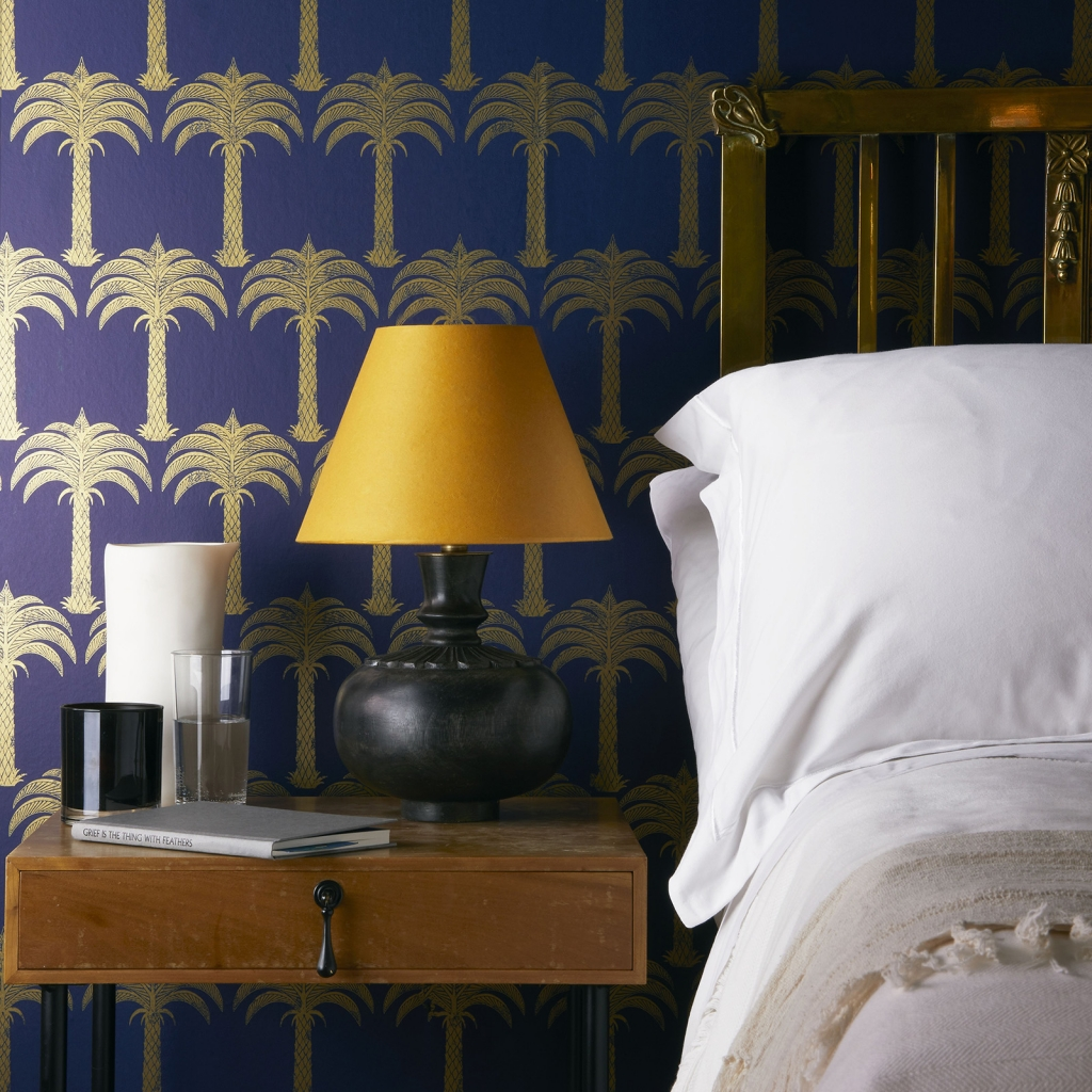 Interior designer Sophie Robinson talks about interiors mustard trend, Pooky Orchy table lamp on bedside table white bedlinen