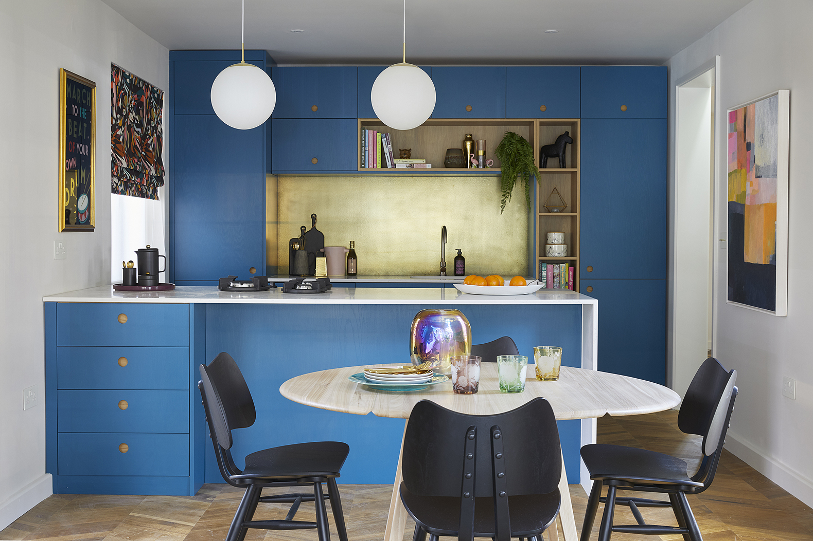 marine blue kitchen by naked kitchens designed by sophie robinson for the ideal home show. gold kitchen splash back, gold kitchen taps and ercol mid century modern table and chairs