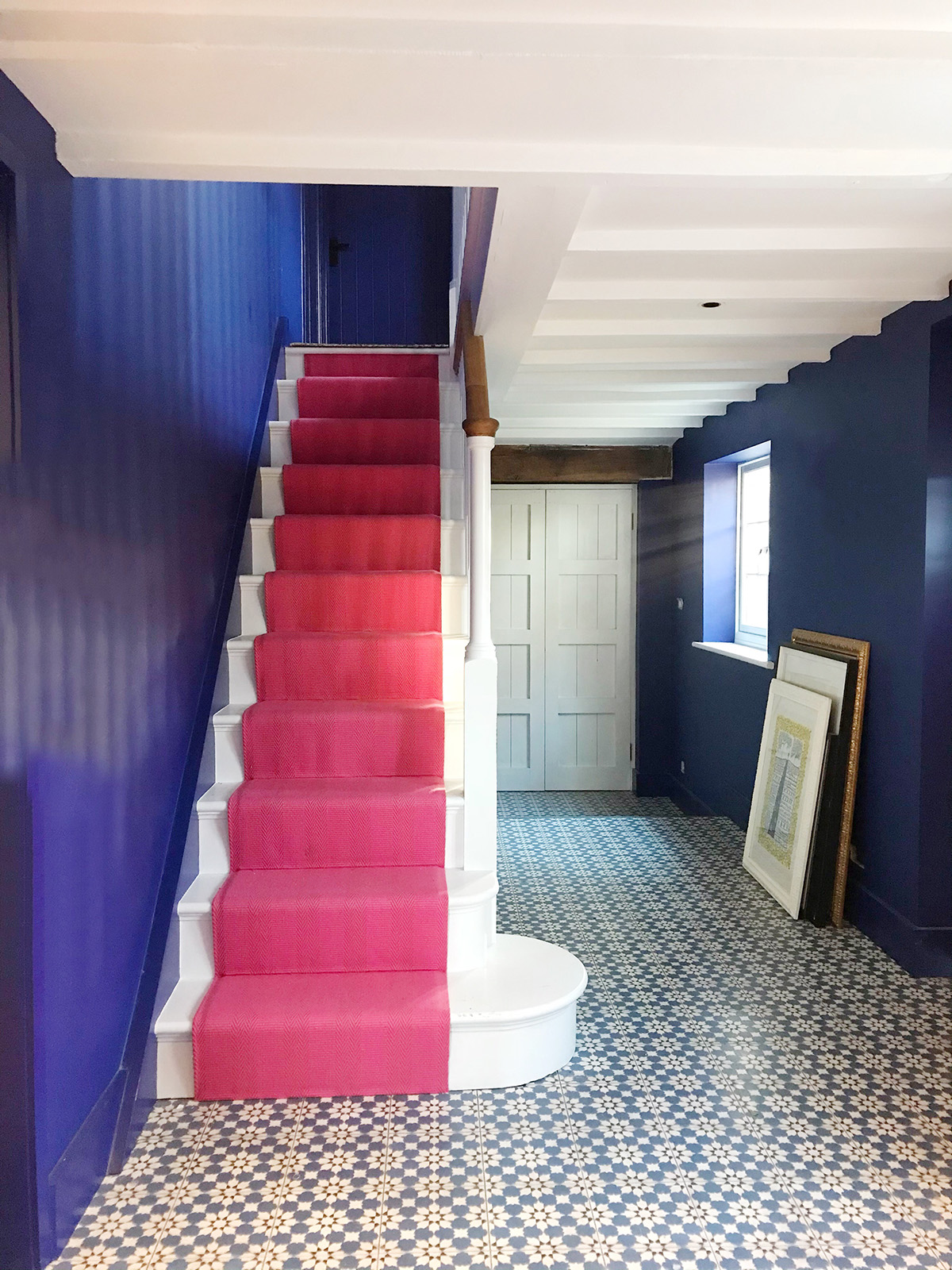 interopr designer Sophie Robinsons hallway is painted in Zoffanys Lazuli blue and has a bright pink stair runner. The cement tiles are by Claybrook studio