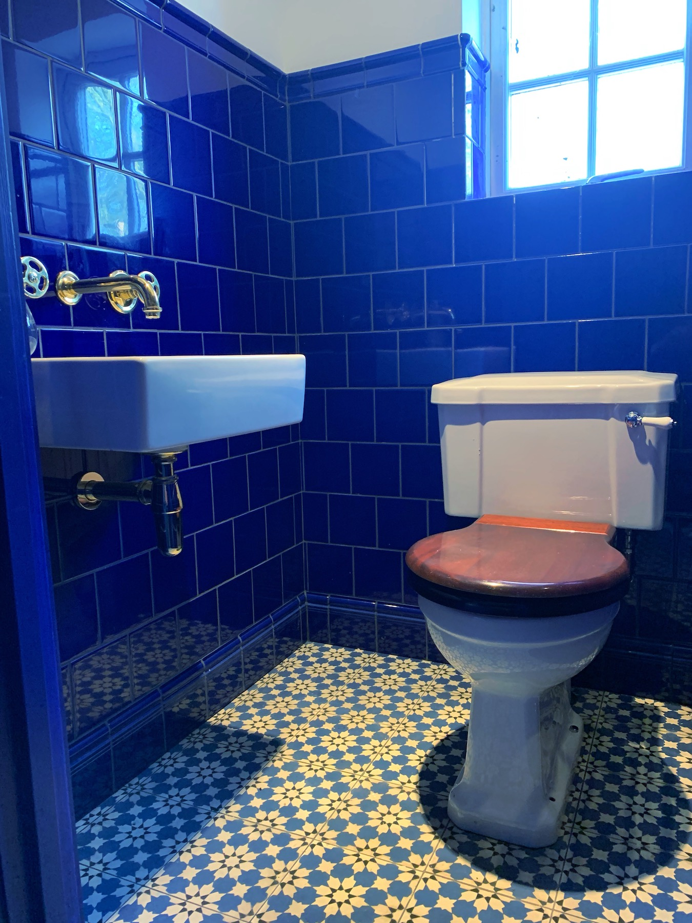 The down stairs loo tiled in deep dark blue tiles from Milton Hollis in the home of interior designer Sophi Robinson