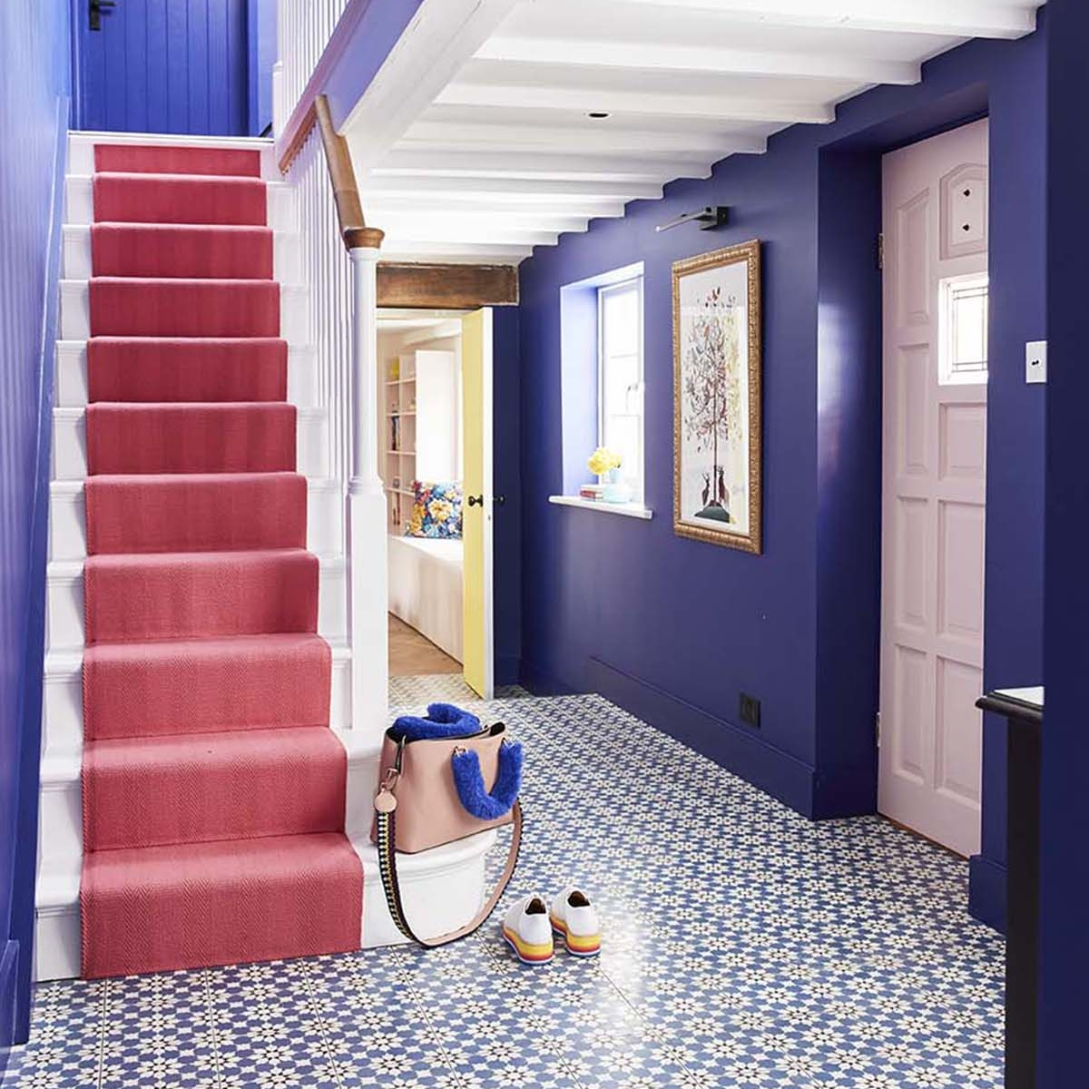 At home with interior designer Sophie Robinson. Her bright and cheery hallway has dramatic bluewalls painted in Lapis by Zoffany, blue patterned tiles by Claybrook and a bright Rose stair runner by Roger Oates