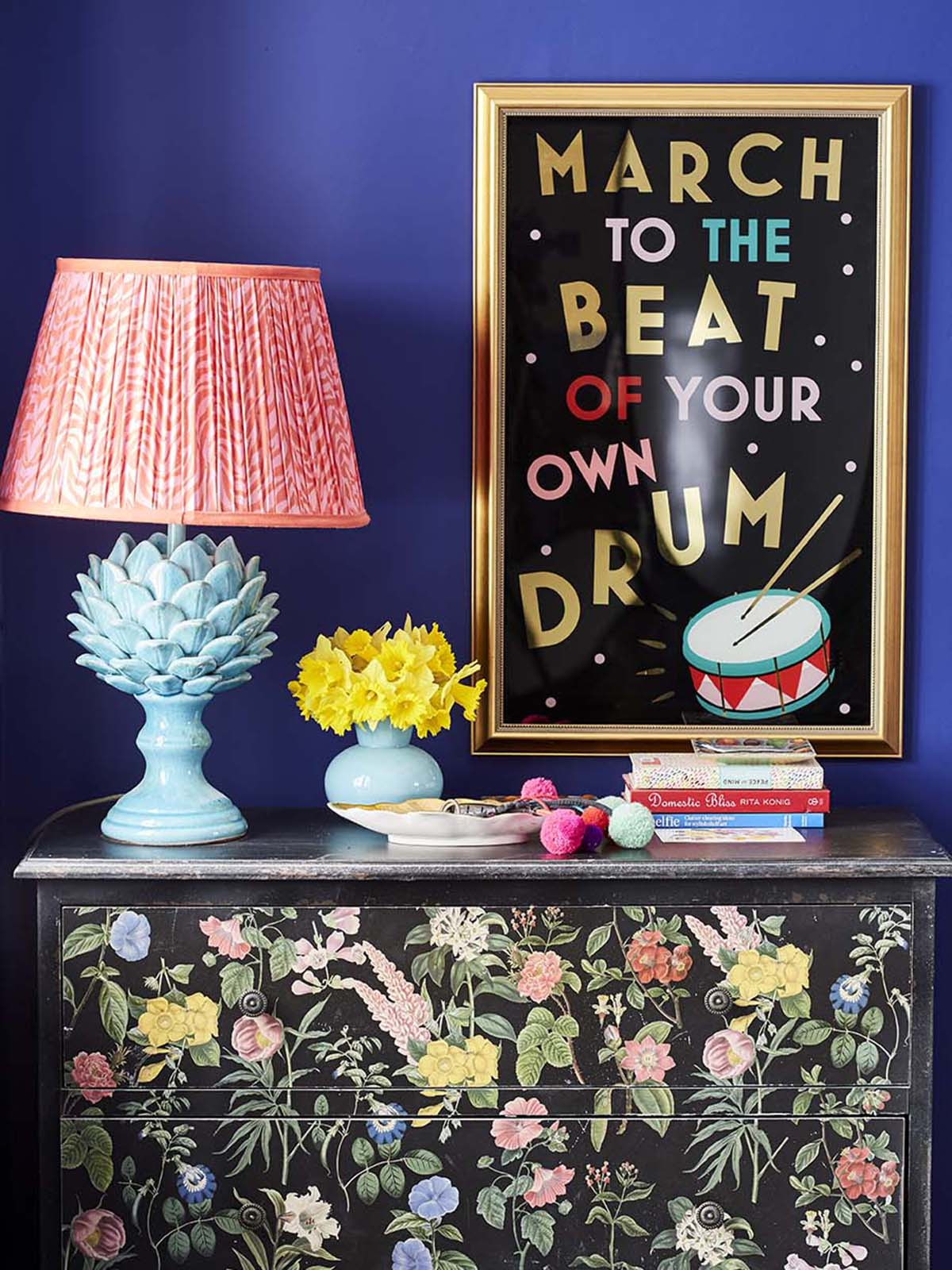Colour queen Sophie Robinson reveals her renovated hallway featuring vibrant blue walls painted in Zoffany's Lapis and a unique black sideboard with multi-coloured floral design