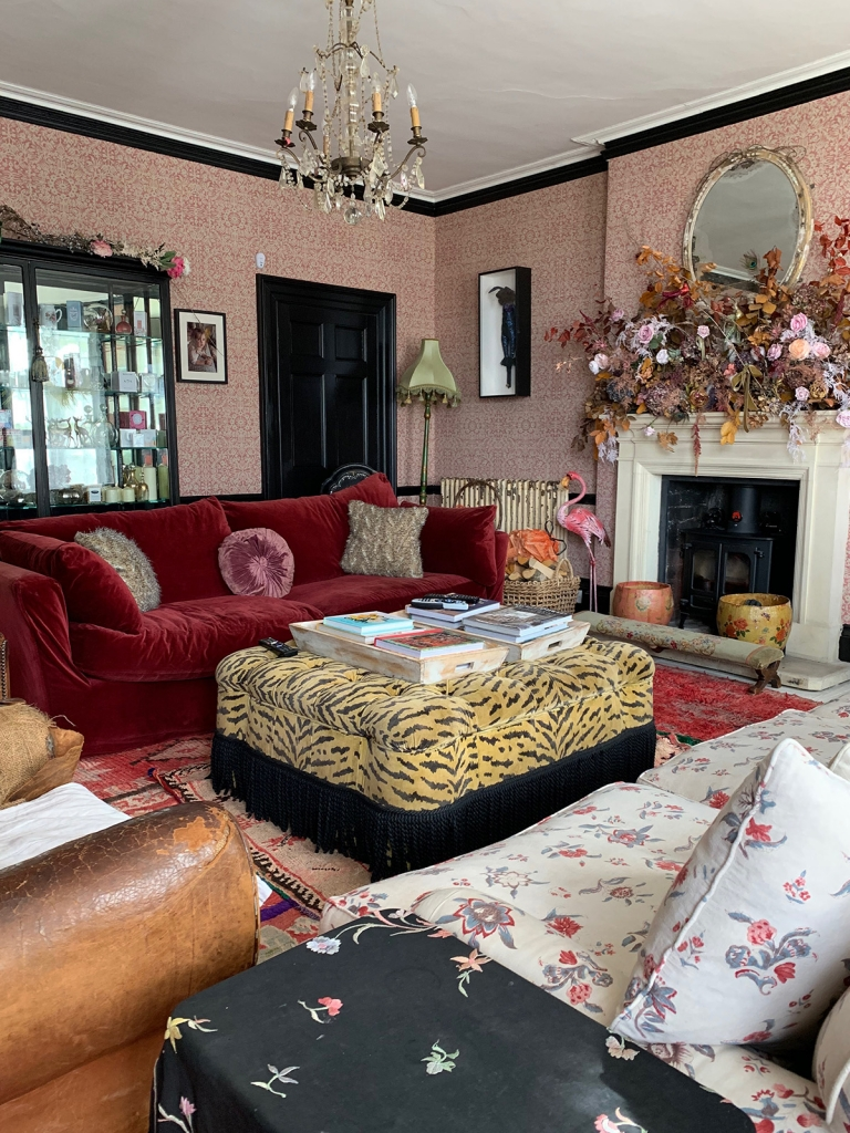 home of pearl lowe's living room with red velvet sofa, robert kime wallpaper and tiger print footstool