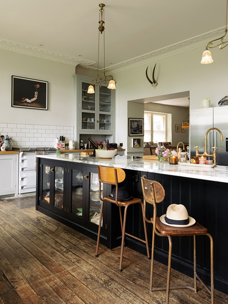 black devol kitchen with carrera marble work tops, brass taps, vintage 1930's lights, modern art, metro tlies and vintage 40's bar stools in the home of pearl lowe