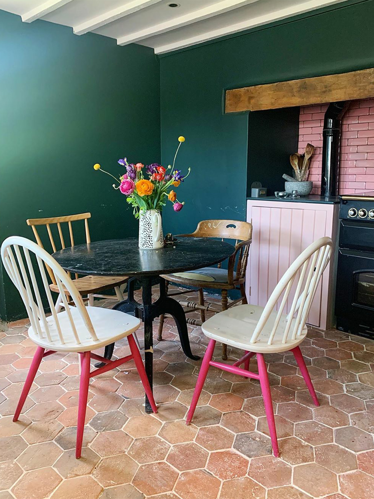 country kitchen in dark green with mid century modern ercol chairs and pink kitchen tiles. Reclaimed hexagon terracotta floor tiles complete the modern country look